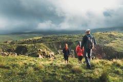 Grupo de caminantes que caminan a lo largo de las colinas verdes, vista posterior Concepto del descubrimiento del turismo del via foto de archivo