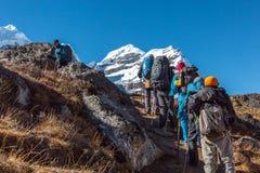 Grupo de caminantes que caminan para arriba en rastro de montaña escarpado imágenes de archivo libres de regalías