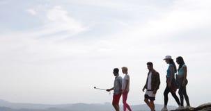 Grupo de caminhada dos turistas em homens e em mulheres felizes guardando superiores da câmera da ação da montanha sobre a skylin vídeos de arquivo