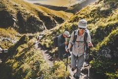 Grupo de caminhantes que andam avante em montanhas do verão, conceito do passeio na montanha do curso da viagem imagem de stock