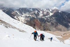 Grupo de caminhantes que andam no terreno da neve e do gelo Foto de Stock