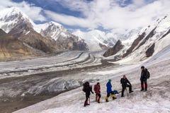 Grupo de caminhantes que andam no terreno da neve e do gelo Imagens de Stock