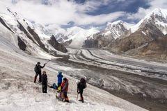 Grupo de caminhantes que andam no terreno da neve e do gelo Fotografia de Stock Royalty Free
