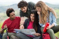 Grupo de caminhantes que olham o mapa Imagem de Stock