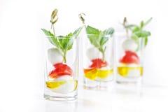 Grupo de canapes no vidro com gre do mozarella, do tomate e do azeite Fotografia de Stock Royalty Free