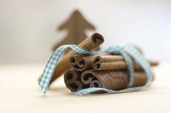Grupo de canela atado con el arco azul claro a cuadros, árbol de navidad de madera Fotos de archivo libres de regalías