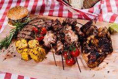 Grupo de carne grelhada na placa de madeira Imagem de Stock