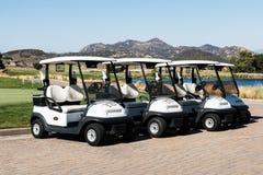 Grupo de carros de golf cerca de un lago y de montañas en el club de golf de la cala de Barona fotos de archivo libres de regalías