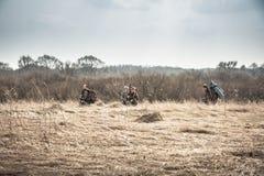Grupo de cazadores que ocultan en campo rural con la hierba seca durante temporada de caza en día cubierto Foto de archivo libre de regalías