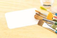 Grupo de cepillo de la acuarela y de tarjeta en blanco del Libro Blanco en la etiqueta de madera Foto de archivo