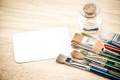 Grupo de cepillo de la acuarela y de tarjeta en blanco del Libro Blanco en la etiqueta de madera Fotografía de archivo libre de regalías