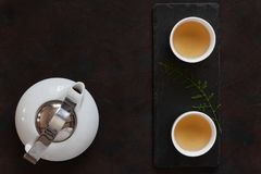 Grupo de chá asiático da porcelana branca com leite Oolong do chá verde na mesa de pedra preta Feche acima, vista superior imagem de stock royalty free