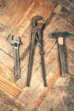 Grupo de chave inglesa ajustável, de chave de tubulação e de martelo no floo de madeira Imagens de Stock Royalty Free