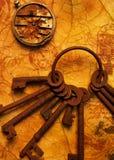 Grupo de chaves com engrenagens no papel velho. Fotos de Stock