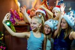 Grupo de chicas jóvenes alegres que celebran la Navidad Selfie Fotografía de archivo