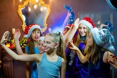 Grupo de chicas jóvenes alegres que celebran la Navidad Selfie Imagen de archivo