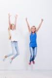 Grupo de chicas jóvenes felices que saltan en blanco Fotografía de archivo