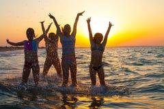 Grupo de chicas jóvenes felices que saltan en la playa Foto de archivo