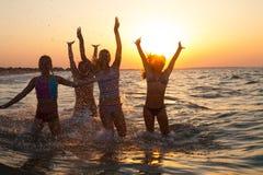 Grupo de chicas jóvenes felices que saltan en la playa Imagen de archivo libre de regalías