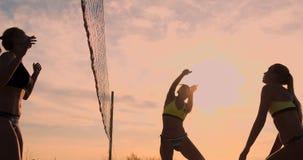 Grupo de chicas j?venes que juegan a voleibol de playa durante puesta del sol o salida del sol almacen de video