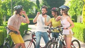 Grupo de ciclistas alegres que descansan en parque almacen de metraje de vídeo