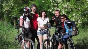 Grupo de ciclistas que comprueban el mapa en tableta que discute la ruta almacen de video