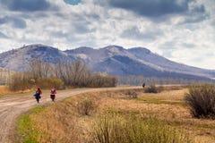 Grupo de ciclistas que viajan que cruzan el campo Imágenes de archivo libres de regalías