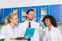 Grupo de científicos del laboratorio que examinan el líquido verde en el tubo de ensayo usando las tabletas, raza Team Of Lab Wor Fotos de archivo