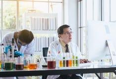 Grupo de cientista asiático que trabalha e que explica a informação da pesquisa junto no laboratary imagens de stock