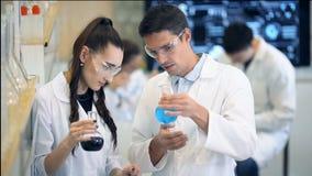 Grupo de cientistas do laboratório que discutem sua pesquisa no laboratório video estoque