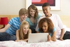 Grupo de cinco adolescentes usando la computadora portátil en dormitorio Fotos de archivo libres de regalías