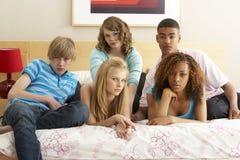 Grupo de cinco amigos adolescentes que parecen aburridos en cama Fotografía de archivo libre de regalías