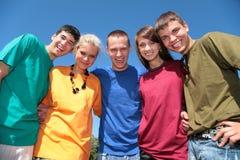 Grupo de cinco amigos en camisas multicoloras Fotos de archivo libres de regalías