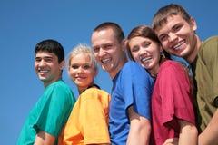 Grupo de cinco amigos en camisas multicoloras Imágenes de archivo libres de regalías