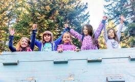 Grupo de cinco amigos femeninos de la escuela que llevan a cabo las manos en el playgro Imagenes de archivo