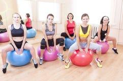 Grupo de cinco atletas fêmeas caucasianos que têm exercícios com Fitballs fotografia de stock royalty free