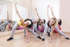 Grupo de cinco desportistas profissionais que fazem o esticão de exercícios com o tronco que dobra-se na classe do esporte Imagem de Stock Royalty Free