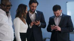 Grupo de cinco hombres de negocios multirraciales que colocan y que usan smartphones metrajes