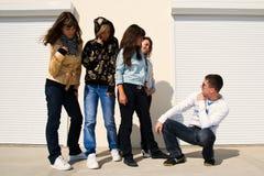 Grupo de cinco personas jovenes cerca de la pared blanca Fotografía de archivo libre de regalías