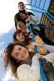 Grupo de cinco personas jovenes sonrientes en las escaleras Fotos de archivo