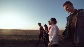 Grupo de cinco personas que caminan a lo largo del camino de tierra almacen de metraje de vídeo