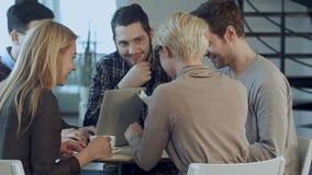 Grupo de cinco personas que discuten algo con sonrisa mientras que se sienta en la tabla de la oficina metrajes