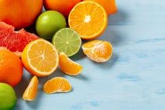 Grupo de citrinas inteiras e cortadas - tangerinas, lim?es, cais, laranjas, toranjas na superf?cie do azul fotografia de stock