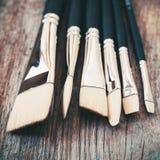 Grupo de close up dos pincéis do artista na tabela de madeira rústica Foto de Stock Royalty Free