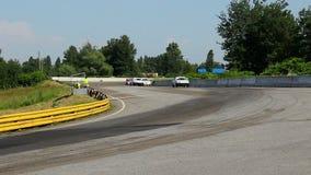 Grupo de coches de carreras que acometen, tomando la vuelta aguda, compitiendo para la taza almacen de video