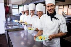 Grupo de cocineros que sostienen la placa de postres delecious en cocina imagenes de archivo