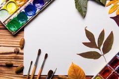 Grupo de coleção dos acessórios do artista com folhas de outono Lona para pintar, escovas da arte, paleta imagens de stock