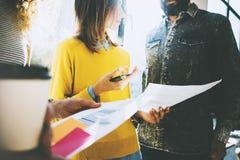 Grupo de colegas de trabalho novos que discutem a ideia do negócio Mulher que guarda papéis em suas mãos e que fala com um colega Imagens de Stock Royalty Free
