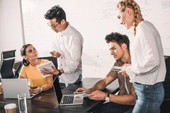 grupo de colegas multiétnicos del negocio que tienen reunión con los ordenadores portátiles y la tableta digital en moderno imagen de archivo libre de regalías