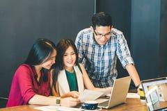 Grupo de colegas ou de estudantes universitário asiáticas novas do negócio na discussão ocasional da equipe, reunião de negócios  imagens de stock